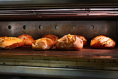 Fresh baked breads in oven at commercial kitchen - p300m2242872 by Jose Luis CARRASCOSA