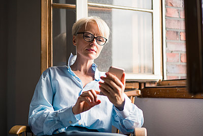Mature businesswoman using mobile phone while sitting on chair at window in home office - p300m2267758 by Robijn Page