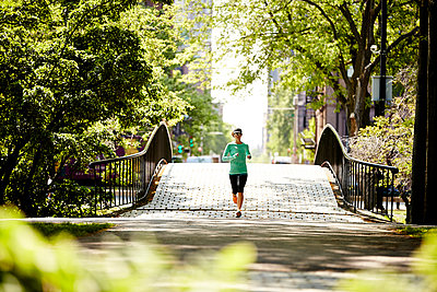 A woman runs along The Esplanade along the Charles River in Boston, MA. - p343m1184461 by Josh Campbell