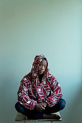 African woman sitting on a stool - p427m2285209 by Ralf Mohr