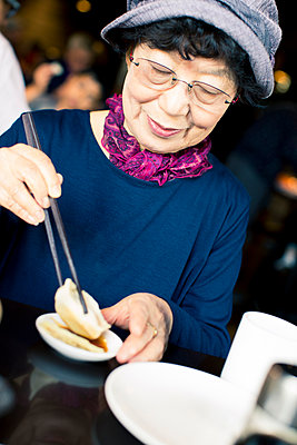 Older Japanese woman eating food with chopsticks - p555m1302172 by Jed Share/Kaoru Share