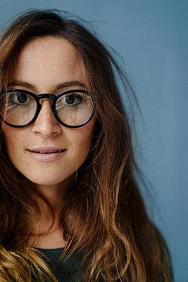 Porträt einer jungen Frau mit Designerbrille - p586m1510381 von Kniel Synnatzschke