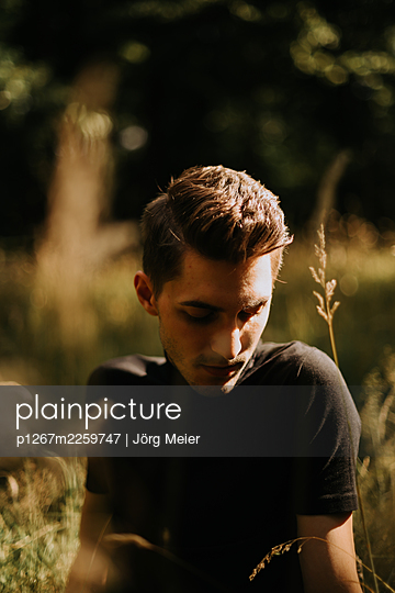 Young man sitting in the meadow - p1267m2259747 by Jörg Meier