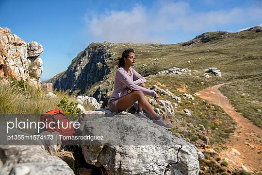 Junge Frau macht eine Pause auf ihrer Bergwanderung - p1355m1574173 von Tomasrodriguez