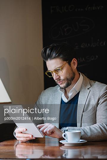 Businessman using tablet in a cafe - p300m2012414 von Alberto Bogo