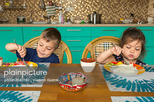 Portrait of boy and his little sister eating breakfast in the kitchen - p300m2043182 by Vladimir Godnik
