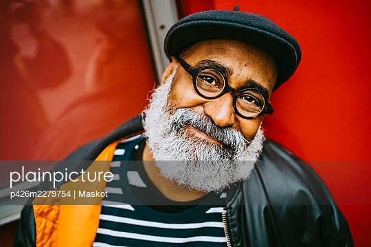 Portrait of smiling bearded senior male hipster wearing eyeglasses and beret - p426m2279754 by Maskot