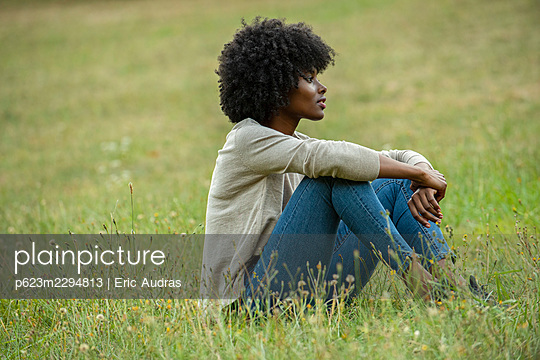 Thoughtful young woman sitting in park - p623m2294813 by Eric Audras