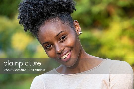 Portrait of smiling young woman in park - p623m2294880 by Eric Audras
