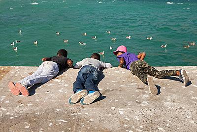3 kleine Jungs spielen am Wasser - p045m1362806 von Jasmin Sander