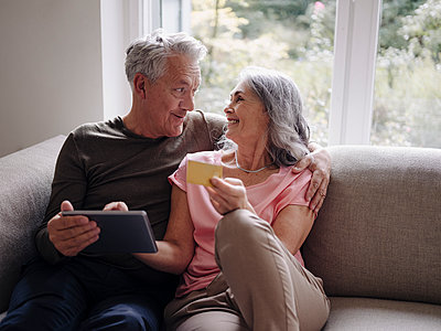 Happy senior couple relaxing on couch at home using tablet for online shopping - p300m2156214 by Gustafsson