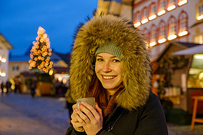 Happy woman wearing fur hood while holding coffee cup at Christmas market - p300m2202781 by Lisa und Wilfried Bahnmüller