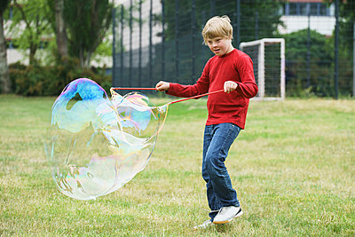 Disabled boy playing with soap bubbles in park - p301m1180551 by Halfdark
