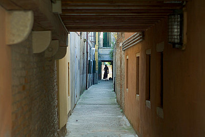 A person standing at the end of an alleyway - p3485909 by Ture Westberg