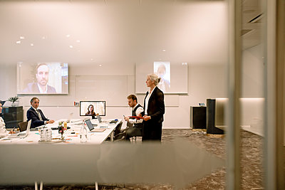 Mature businesswoman giving presentation in board room during global conference meeting at office - p426m2186876 by Maskot