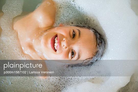 Portrait of happy little girl bathing in a tub - p300m1587102 von Larissa Veronesi