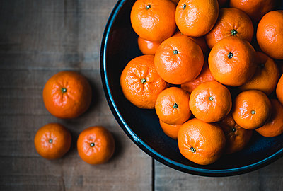 Bowl of mandarin oranges on wooden table with some scattered on table. - p1166m2094811 by Cavan Images