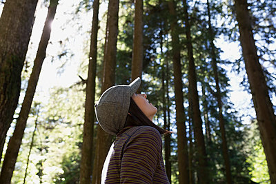 Woman looking up at tall trees in woods - p1192m1149490 by Hero Images