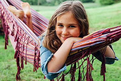Portrait of smiling girl lying in hammock - p300m1587382 by Annie Hall