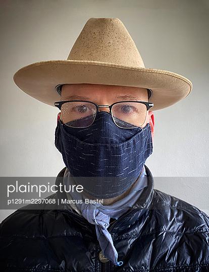 Cowboy with cloth face mask, portrait - p1291m2297068 by Marcus Bastel