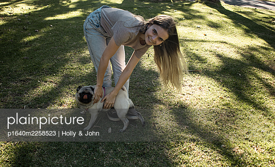 Teenage girl playing with dog in the park - p1640m2258523 by Holly & John