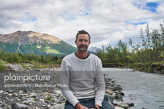 Man relaxing by stream, scenic view in background, Chitina, Alaska, United States - p924m2097672 by Matt Hoover Photo