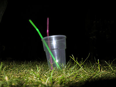 Empty plastic glass with straws on grass at night - p1072m829366 by Neville Mountford-Hoare