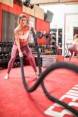 Young slim Caucasian woman working out with battle ropes in the gym - p1166m2084304 by Cavan Images