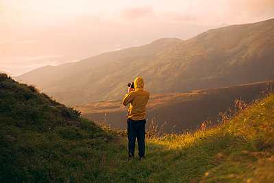 Man in yellow jacket taking photographs in the Carpathian Mountain Range - p1427m2077592 by Dima Bilous