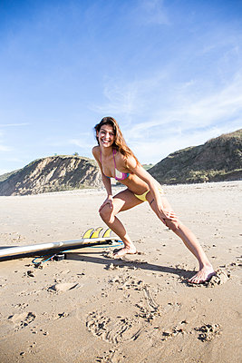 Happy woman carrying stretching on the beach - p300m1204779 by Andrés Benitez