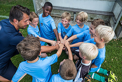 Coach and young football players huddling - p300m1581316 by Fotoagentur WESTEND61