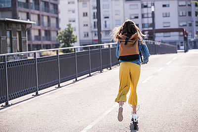 Rear view of young woman riding electric scooter on a bridge - p300m2132574 by Uwe Umstätter