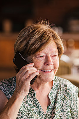 Senior woman smiling while talking on mobile phone at cafe - p300m2226073 by DREAMSTOCK1982