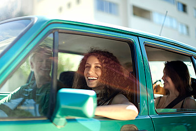 Smiling woman looking away while sitting with friends in car - p300m2264564 by LOUIS CHRISTIAN