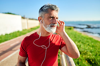 Contemplating man with earphones looking away by the sea - p300m2275684 by Kiko Jimenez