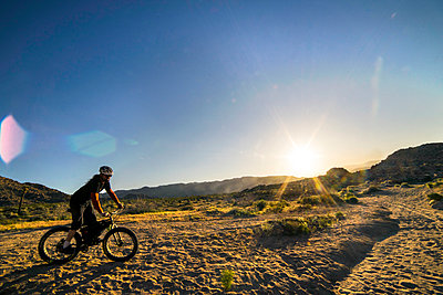 Mountain biker riding on dirt track - p343m1475629 by Cavan Images