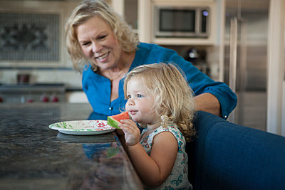 Grandmother watching granddaughter eating watermelon in kitchen - p555m1408694 by Shestock