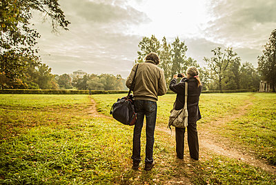 Caucasian couple standing on trail in park with camera - p555m1413194 by Aleksander Rubtsov