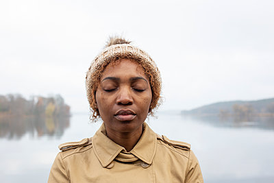 Dark-skinned woman with closed eyes by the lake - p975m2228554 by Hayden Verry