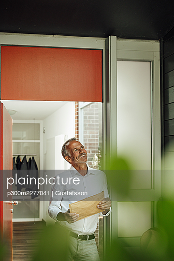 Smiling thoughtful man holding package while leaning at doorway - p300m2277041 by Gustafsson