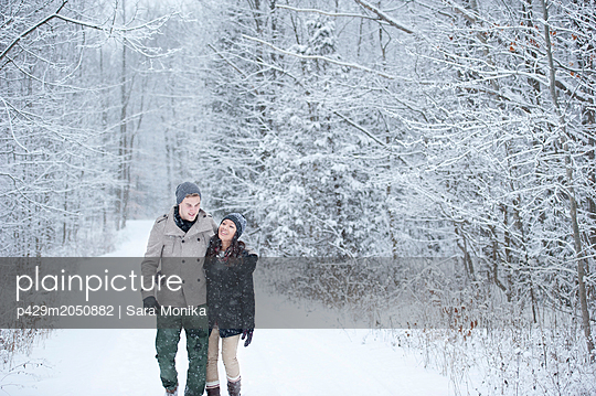 Romantic young couple strolling in snowy forest, Ontario, Canada - p429m2050882 by Sara Monika