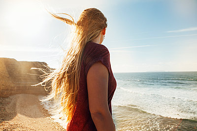 Side view of woman looking at view while standing at beach on sunny day - p1166m1186550 by Cavan Images