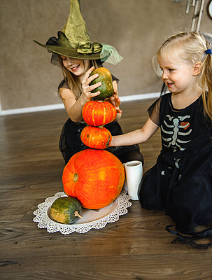 Two Sisters Dressed for Halloween in Skeleton Costumes with Pumpkins - p1166m2147256 by Cavan Images