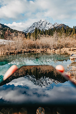 Mountain reflects in a smartphone - p1455m2081766 by Ingmar Wein