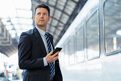 Businessman with cell phone on station platform - p300m2102984 von Daniel Ingold