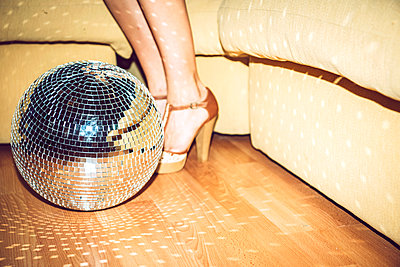 Young woman wearing high heels standing by disco ball on floor in party - p300m2206673 by klublu