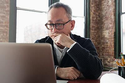 Asian businessman using laptop in office - p555m1311700 by Jose Luis Pelaez Inc