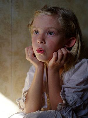 Staunendes Mädchen stützt Kopf auf ihre Hände - p945m1465915 von aurelia frey