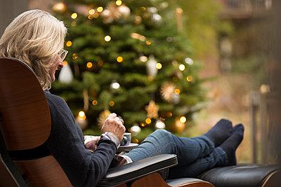 Frau sitzt gemütlich im Sessel vor geschmücktem Weihnachtsbaum und trinkt Tee. - p948m2014773 von Sibylle Pietrek
