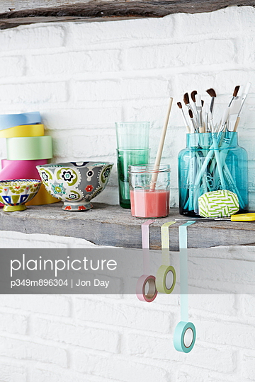 Paintbrushes and tapes with decorated bowl on shelf in whitewashed room - p349m896304 by Jon Day